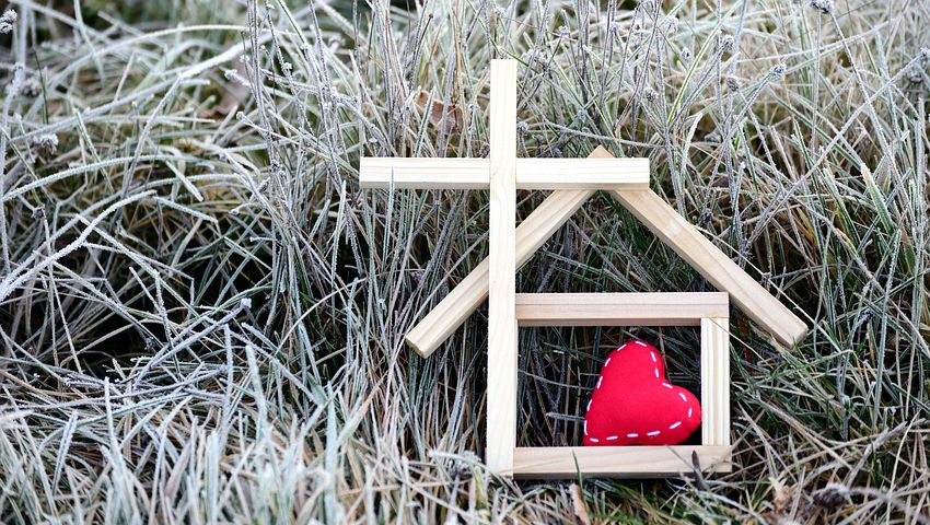 stick forming cross and house with a red heart inside.