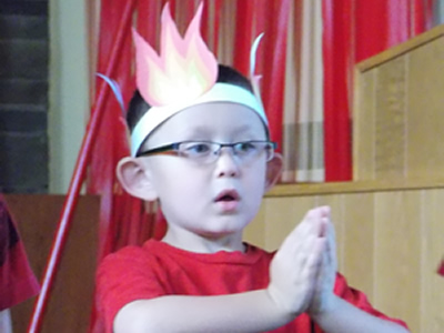 Boy with a paper crown on his head praying