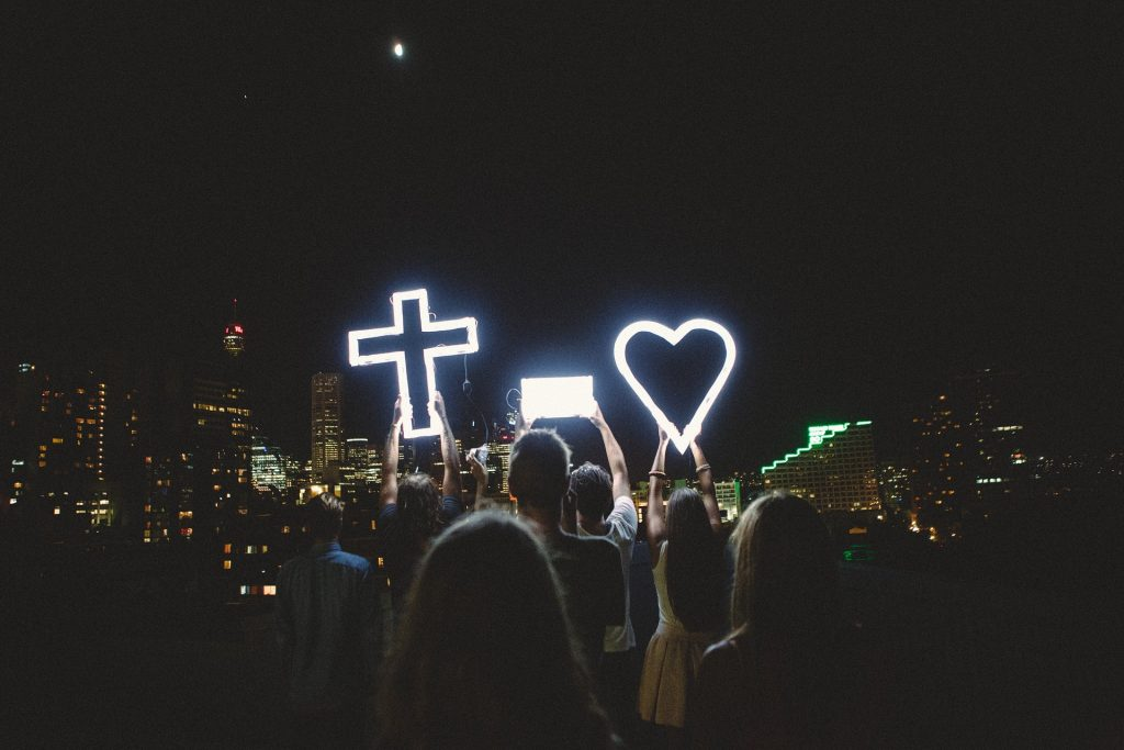 crowd of people at night holing a lighted cross and heart