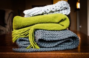 three folded crocheted blankets